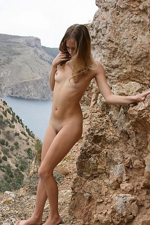 Pretty female amateur poses in the nude at the rock