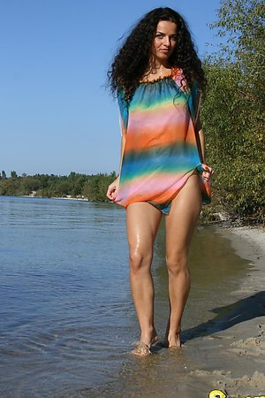 Slim brunette undressing on the beach and playing in the warm water