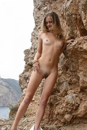 Cute girl undressing and posing nude on the rocks at the beach