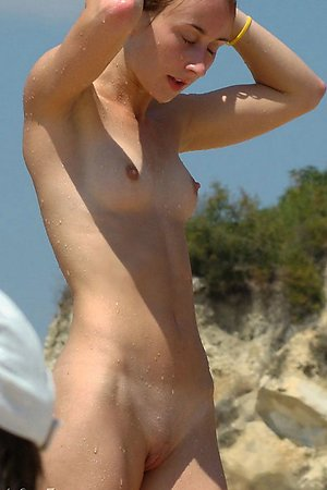 liberated young nymphomaniac warms naked vagina in the sun among nudists on the beach