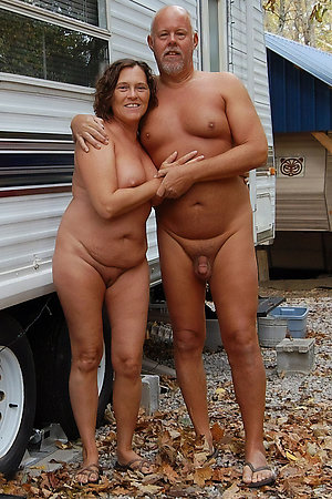 Naturists of different age near houses and trailers
